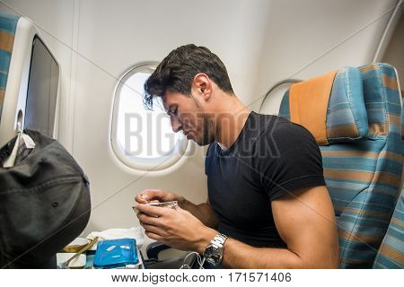 Young man feeling disgusted after tasting insipid food in the airplane. Horizontal indoors shot.