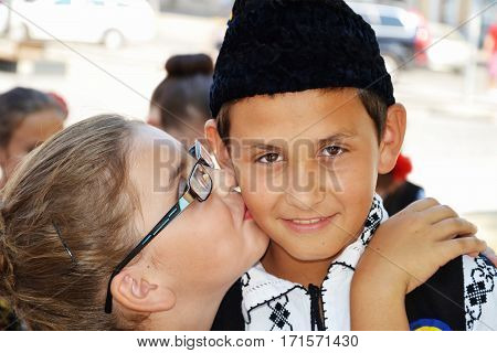 CLUJ-NAPOCA ROMANIA - AUGUST 04 2012: Young girl kisses boy and hugs him on the street. The boy dressed in Romanian traditional folk costume has a surprised or embarrassed face expression.