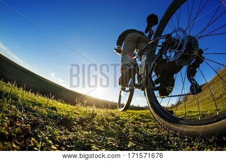 Young Cyclist riding on the Beautiful Meadow Trail on sunny day. Detail of the bicycle. Wheel. WIde angle. Travel in the countryside. Spring season. Fisheye.