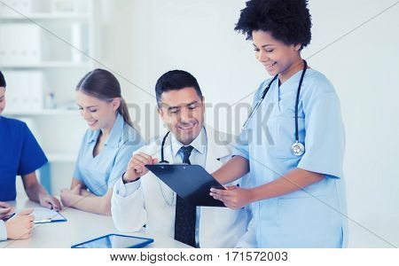 hospital, profession, people and medicine concept - group of happy doctors with clipboard meeting and discussing something at medical office