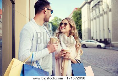 sale, consumerism and people concept - happy couple with shopping bags and coffee paper cups at shop window in city