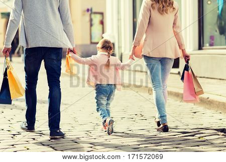 sale, consumerism and people concept - close up of happy family with little child and shopping bags in city