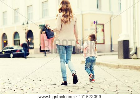 sale, consumerism and people concept - close up of mother and child with shopping bags walking along city street