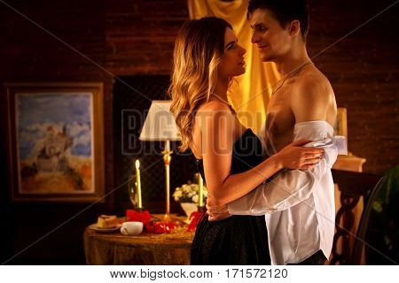 Couple dancing and kissing indoor. Romantic evening interior for loving couple. Loving people undress in intim interior. A lot of pictures in room.