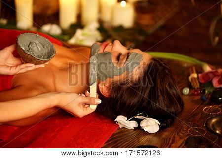 Mud facial mask of woman in spa salon. Massage with clay full face . Girl on interior with oriental therapy room. Female with flower lying wooden spa bed. Beautician's hand with bowl therapeutic mud.