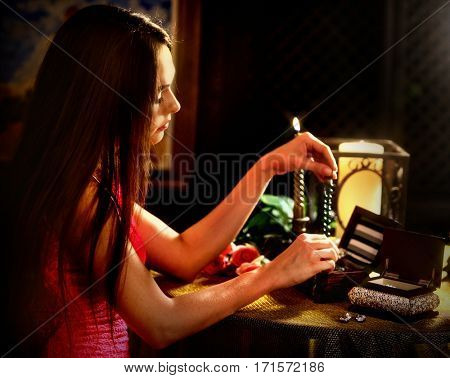 Woman over jewelry box puts necklace on her neck . Romantic evening on luxary interior background.