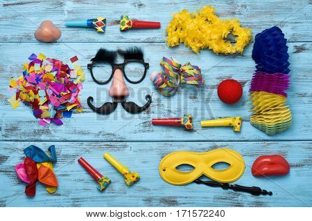 high-angle shot of different fancy dress party items on a blue wooden surface, such as a pair of fake black glasses with nose and mustache, a clown nose, some party horns, confetti or a handled mask