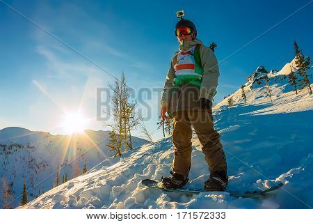 Freeride Snowboarder Stands On Hillside In Light Dawn Sun