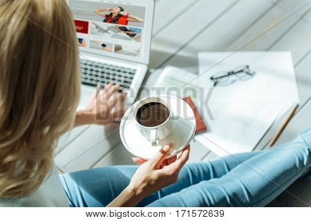 Creative and hardworking. Close up of young pretty ambitious womans hands holding a cup of coffee and using laptop while spending time at home.