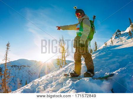 Freeride Snowboarder Stands On Hillside At Dawn And Shows His Ha