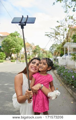 Indian woman in white summer dress crouching and embracing her little daughter with funny toy while taking photograph of themselves