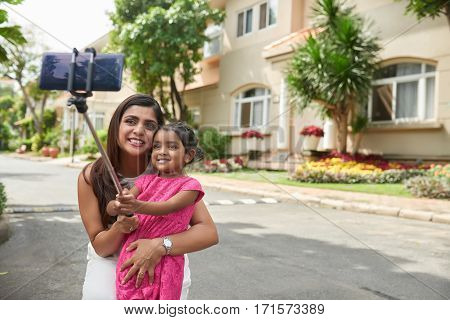 Funny little Indian girl in bright pink dress holding monopod in hands and taking selfie with her beautiful mother