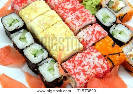 Appetizing sushi pieces with chopsticks on white plate isolated top view closeup
