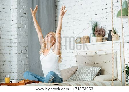 Good morning. Pretty relaxed young woman stretching herself while sitting in bedroom and preparing to have breakfast.