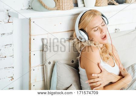Best songs. Glad young pretty woman listening to music in bed while posing and using headphones.