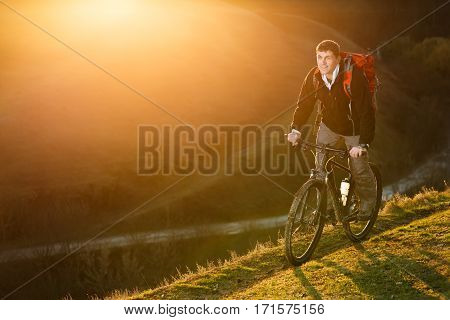 Mountain biker riding on bike in spring inspirational mountains landscape. Man cycling MTB on trail track. Sport fitness motivation and inspiration outdoors in sunset. Cycclist with red backpack.