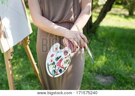 Young girl painter holds a palette with oil paints in her hands on a green background. Nearly stands an easel