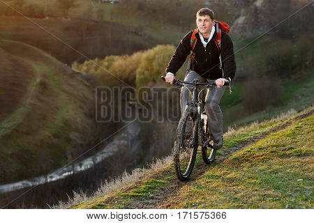 Cyclist Riding the Bike on the Beautiful Spring Mountain Trail. Landspace with hill and pathes. Travel in countryside. Healthy lifestyle. Cyclist with red backpack.