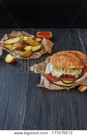 Fast food restaurant dish top view. Meat cheese burger in craft paper, potato chips and wedges. Take away set on dark black wood background. Hamburger and spicy tomato sauce. Vertical