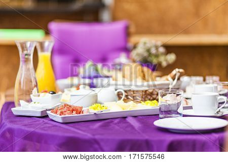 Fresh Breakfast or brunch with ham eggs bread yogurt fruits and coffee on violet table and white dishware