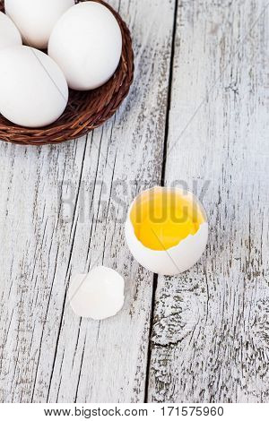 Broke One whole egg amongst white eggs in basket on a white wooden background