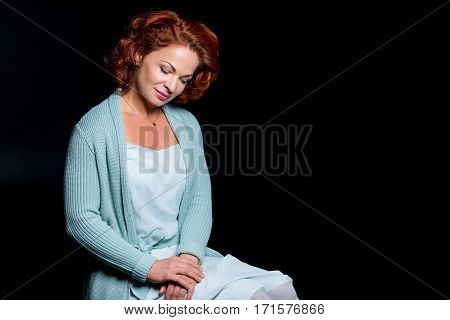 Beautiful mature woman smiling and looking down on black