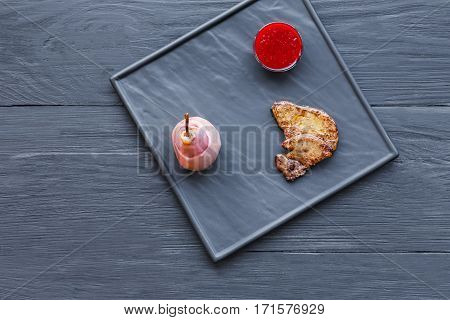 Restaurant dish of haute cuisine top view. Seared foie gras served with berry sauce and pink pear on black slate plate. French delicatessen meal, roasted goose liver.