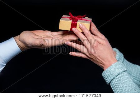 Close-up partial view of woman taking gift box from man ob black