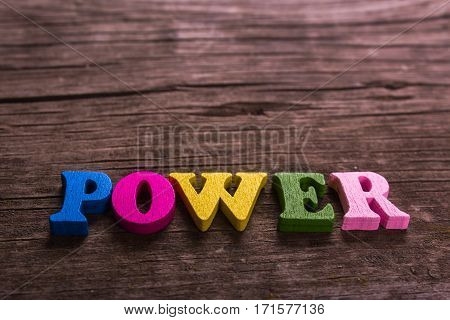 power word made from colored wooden letters on an old table. Concept