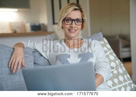 Beautiful blond woman websurfing on laptop at home