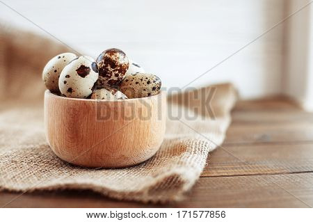 A wooden bowl of quail eggs on the table. The concept of healthy eating and vegetarianism.