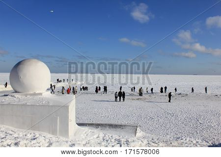 The picture was taken in Odessa in the Ukraine. The picture shows people walking along the beach near the frozen sea. Before that there were severe frosts and the sea in the bay of Odessa froze.