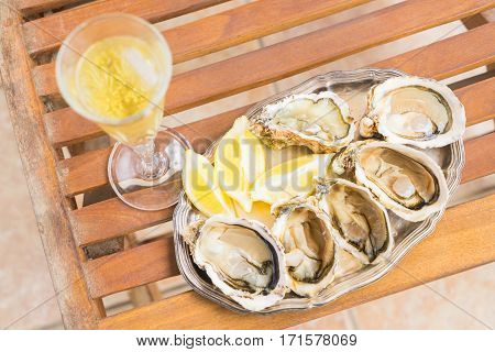 Raw oysters shells and glass of champagne, top view