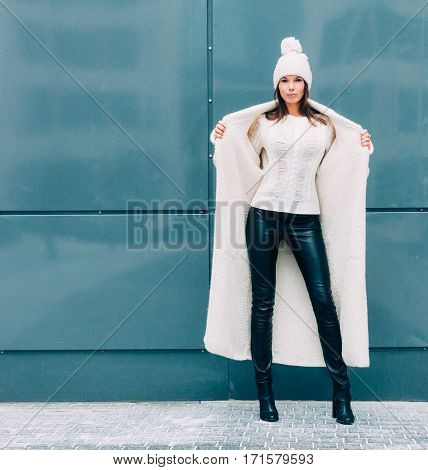Pretty young woman smiling in a knitted hat and a coat on a background of the Europe city. she shows excellent body. Streetstyle.