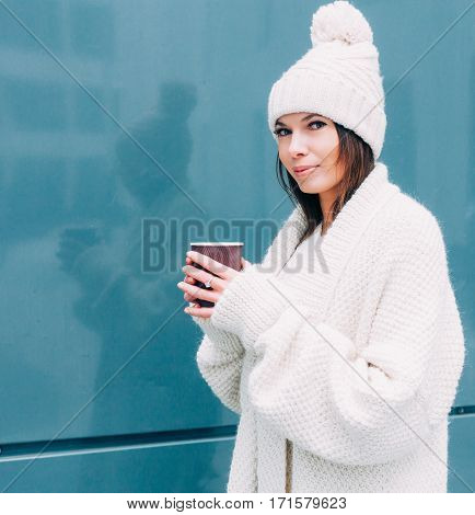 Young hipster looker woman is drinking coffee on the street while walking on cold winter day. Model wearing white coat. Glamorous trendy outfit, accessories, hot latte, toned instagram colors. Streetstyle.