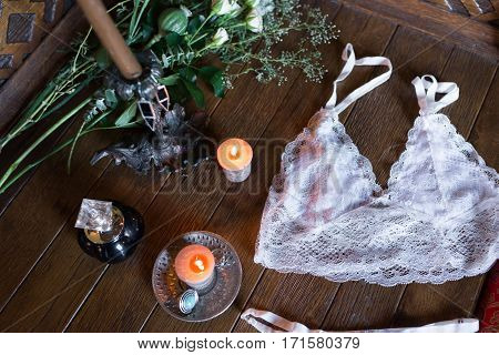 Women's lingerie on the wooden table with candles, perfume and greenery