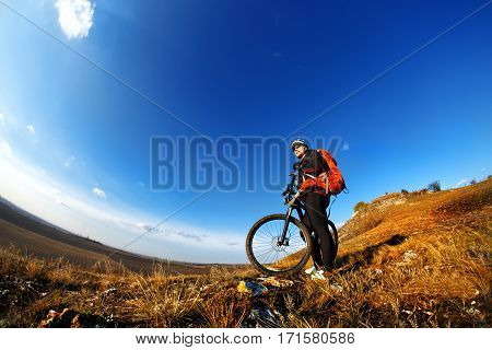 Low, wide angle portrait against blue sky of mountain biker going downhill. Cyclist in black sport equipment and helmet, with red backpack. Wide angle and fisheye. Spring season. Countryside.