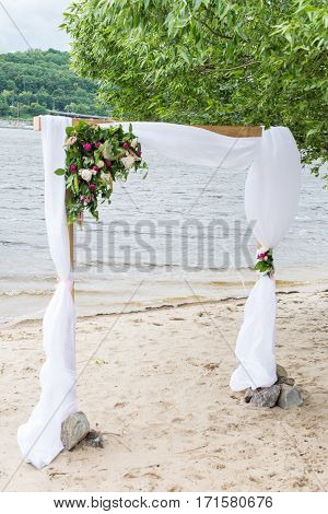 A part of wedding arch with greenery and peonies and river in the background.