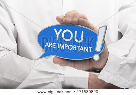 Hand holding a blue bubble speech with the text you are important. Concept of self-confidence training or customer relationship?