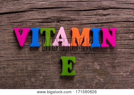 vitamin E word made from colored wooden letters on an old table. Concept