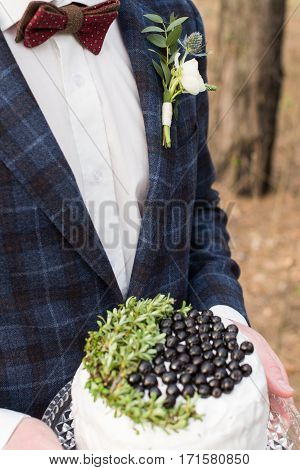 Young groom holding a rustic wedding cake with blueberry and greenery in his hand on a green background. Stylish groom in blue jacket, white shirt and brown bowtie.