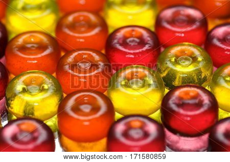 Colorful candy background with yellow orange and pink sweetmeats candies. Dolce vita. Lollipop background closeup.