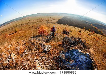 Wide angle view of cyclist standing with mountain bike on trail at sunrise. Cyclist in the helmet and black sunglasses, with red backpack. Landscape with sky, hill and rocks. Fisheye. Spring season. Countryside.