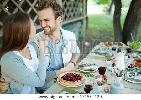 Happy sweethearts sitting by festive table outdoors