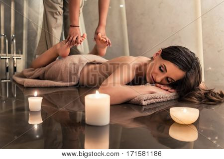 Young woman lying down while enjoying the stretching techniques of a professional Thai massage in luxury spa and wellness center