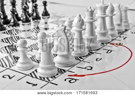 Chess, castling queenside or long castling. White board with chess figures on it. Plan of battle.
