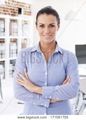 Portrait of confident businesswoman, smiling, standing arms crossed, looking at camera.