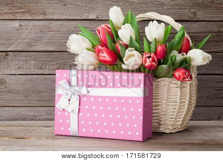 Colorful tulips bouquet and gift box in front of wooden wall. Red and white