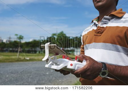 Close-up shot of male hands holding remote controller and playing with drone in sunny park