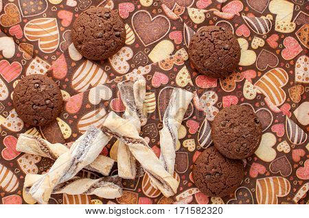 Cookies on dark napkin with image of hearts close up. Top view.